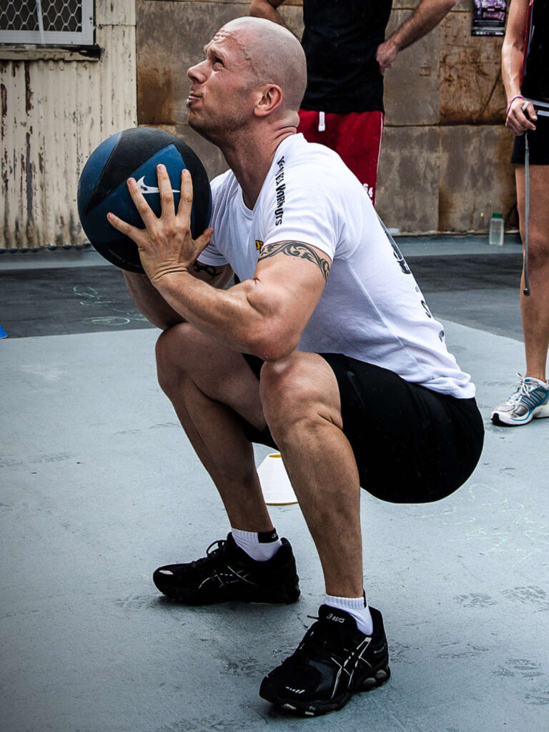 Strong man performing using a weighted medicine ball